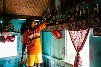 JAIPALGURI, INDIA- AUGUST 16: Player and coach of the female football team, the Dooars XI,  Bhabani Munda, 24, places back one of her 60 football trophies after wiping dust off them on August 16, 2013 at the Kalchini tea estate In Jalpaiguri district , West Bengal, India. The Kalchini tea estate where Bhabani Munda lives is one of the most interior and backwards regions in north Bengal. The tea estates of North Bengal, including the Kalchini tea estate, were in news in 2007-08 for large-scale starvation deaths owing to malnutrition. Even today one person dies every day due to starvation in the north Bengal tea estates. In the last decade there have been 3500 deaths in these tea estates. (Photo by Daniel Berehulak for Time Magazine)