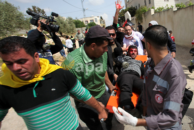 Palestinians carry a wounded protester during clashes with Israeli security forces following a protest Palestinian Prisoner's Day and against the expropriation of Palestinian land by Israel in the West Bank village of Kafr Qaddum, near the northern city of Nablus, April 17, 2015. The current number of Palestinians held in Israeli prisons is at least 6,200 and is the biggest for at least five years, according to figures from rights groups. Photo by Nedal Eshtayah