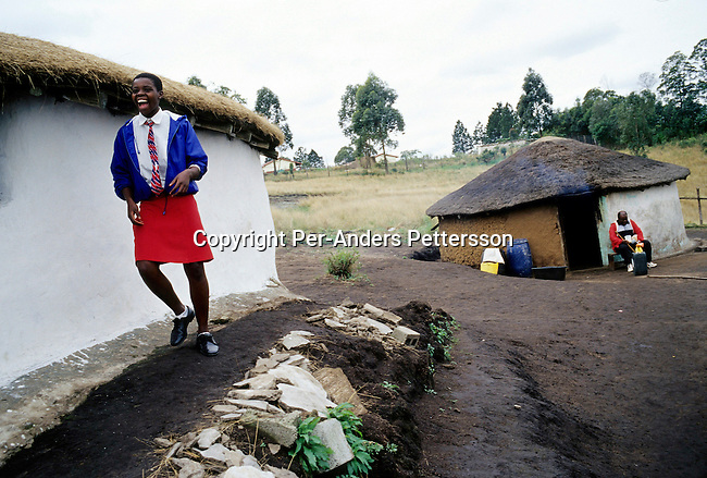 NGUDWINI, SOUTH AFRICA - SEPTEMBER 10: Nobule Ngema, age 16, smiles as she's excited about traveling to the annual Reed Dance on September 10, 2004 in Ngudwini village in rural Natal, South Africa. Nobuhle is traveling on a bus and about 20.000 fellow maidens from all over South Africa is coming to dance for Zulu King Goodwill Zwelethini at the Enyokeni Royal Palace in Kwa-Nongoma about 350 kilometers from Durban. The girls come to the kingdom to declare their virginity and the ceremony encourages girls and young women to abstain from sexual activity to curb the spread of HIV-Aids. Its Nobuhle's first trip and she's already has three virginity certificates as she was tested in the village for the last three years. .(Photo: Per-Anders Pettersson)......