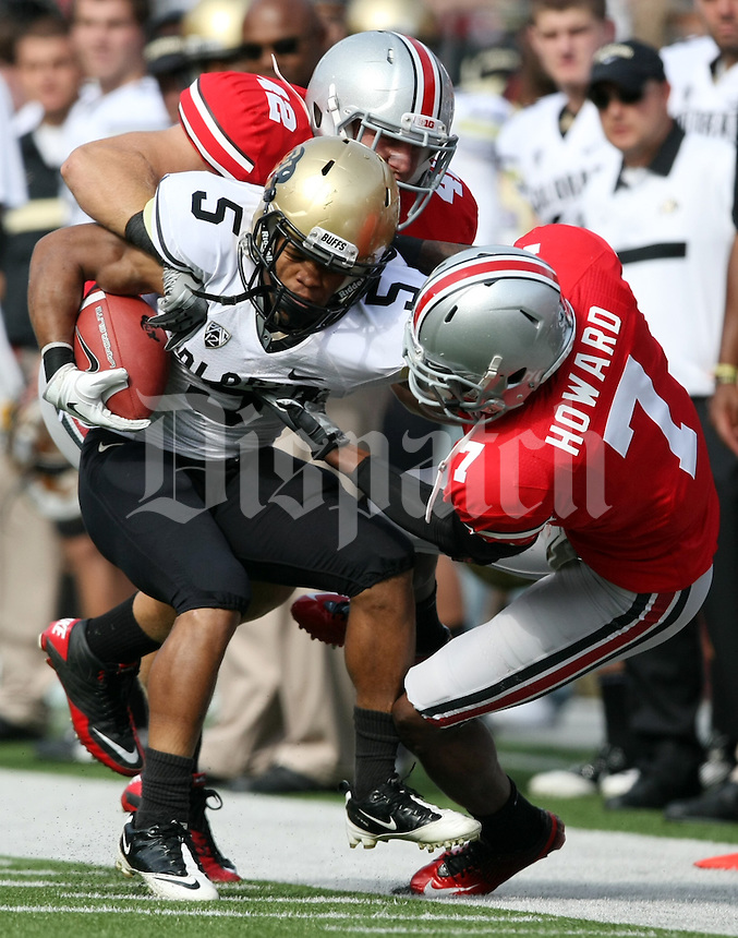Ohio State Buckeyes Andrew Sweat (42) and teammate Travis Howard (7) team up to tackle Colorado Buffaloes running back Rodney Stewart (5) in the first quarter of their NCAA football game at the Ohio Stadium in Columbus, September 25, 2011.  (Dispatch photo by Neal C. Lauron)