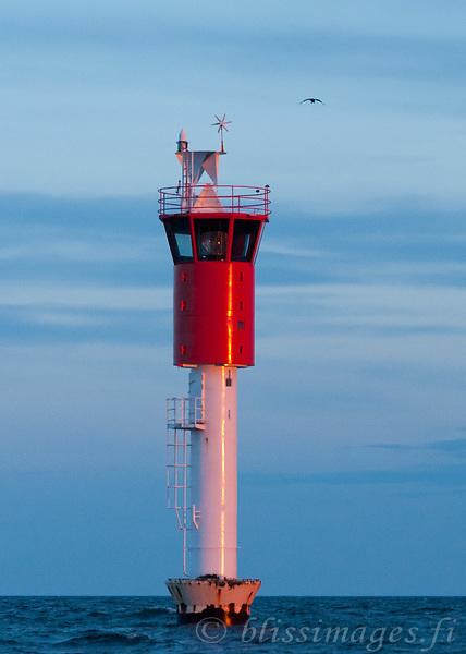 A bird approaches Vaasa Lighthouse at sundown in the Baltic Sea's Gulf of Bothnia, Finland.