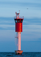 A bird approaches Vaasa Lighthouse at sundown in the Baltic Sea's Gulf of Bothnia, Finland.