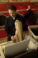 Model Released Photo of a young man and a woman separatly washing their clothes. Photo : 2004, Pierre Roussel