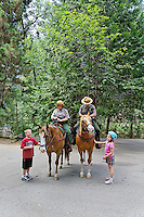 Kids interacting with male and female park rangers on horseback, Yosemite Naional Park, California