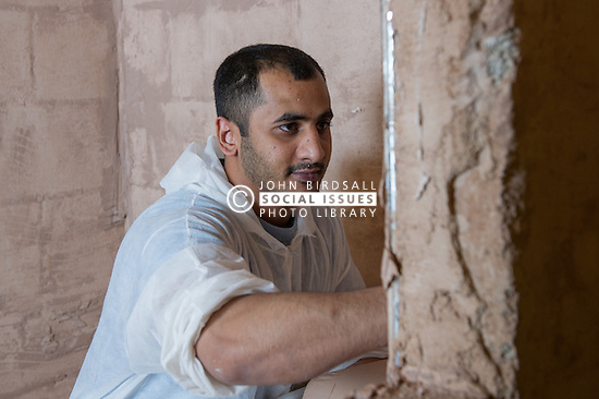 A prisoner learning the plastering trade in a workshop