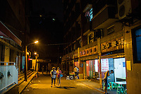 People walk past open-air restaurants in central Yuzhong District, Chongqing, China.
