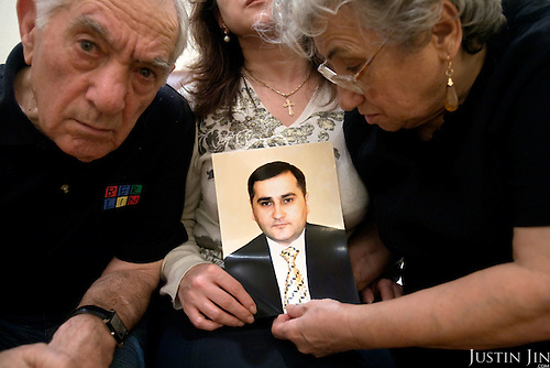 Asya Semenovna Abramian (right), 75, her husband Georgy Saakovich Abramian (left), 76, and their daughter-in-law Marta (centre) with a portrait of Karen Abramian at home in Moscow. Karen Abramian, an ethnic Armenian, was stabbed to death by far right youths in front of his apartment block in Moscow. .Marta Abramian, wife of Karen, does not want to be identified in this photo .for fear of reprisal. .Picture by Justin Jin.