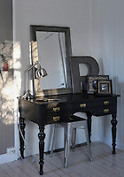 An old 19th century desk has been painted and restored as a dressing table in the master bedroom