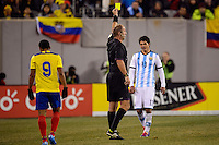 Referee Arbitro Silviu Petrescu cards Argentina defender Facundo Roncaglia (13). Argentina and Ecuador played to a 0-0 tie during an international friendly at MetLife Stadium in East Rutherford, NJ, on November 15, 2013.