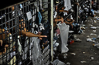 "Mara gang members are seen behind the bars of overcrowded cells at the detention center in San Salvador, El Salvador, 20 February 2014. Although the country's two major gangs reached a truce in 2012, the police holding cells currently house more than 3000 inmates, five times more than the official built capacity. Partly because the ordinary Mara gang members did not break with their criminal activities (extortion, street-level distribution of drugs, etc.), partly because Salvadorean police still applies controversial anti-gang law which allows to detain almost anyone for ""suspicion of gang membership"". Accused young men are held in police detention centers where up to 25 inmates may share a cell of five-by-five metres. Here, in the dark overcrowded cages, under harsh and life-threatening conditions, suspected gang members wait long months, sometimes years, for trial or for to be transported to a regular prison."