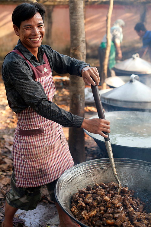 A Cambodian man prepares food for a buddhist wedding in a small village outside of Phnom Penh, Cambodia. <br /> <br /> Photos &copy; Dennis Drenner 2013.