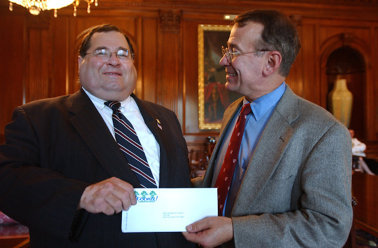 check101201 -- Rep. Jerry Nadler, D-N.Y., left, receives a check from Rep. Greg Ganske, R-Iowa, for rebuilding efforts in New York.   The check in the amount o$10,345.00 is from the city of Altoona, Iowa and represents a dollar from every citizen.