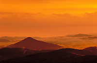 Sunset in Blue Ridge Mountains is reflected in the orange and golden amber glow of the clouds. landscape. sunset, mountains, color. North Carolina, Blueridge Parkway.