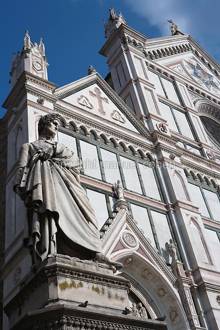Low angle view of statue of Dante, 1865, by Enrico Pezzi, in the Piazza di Santa Croce, Florence, Tuscany, Italy, pictured on June 8, 2007, in the afternoon, with the facade of the Basilica di Santa Croce, (Basilica of the Holy Cross), 1294, in the background. Dante Alighieri, Italian poet, (1265-1321) wrote the Divine Comedy and was active in Florentine politics. The Basilica di Santa Croce is the main Franciscan church in Florence. The neo-Gothic marble facade, 1857-63, was designed by Nicolo Matas. Florence, capital of Tuscany, is world famous for its Renaissance art and architecture. Its historical centre was declared a UNESCO World Heritage Site in 1982. Picture by Manuel Cohen. vertical,