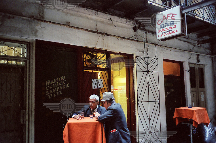 Two men drinking at a table outside a bar. /Felix Features