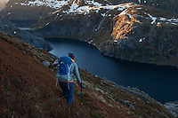 Female hiker descends steep mountain slope from Støvla mountain peak, Moskenesøy, Lofoten Islands, Norway