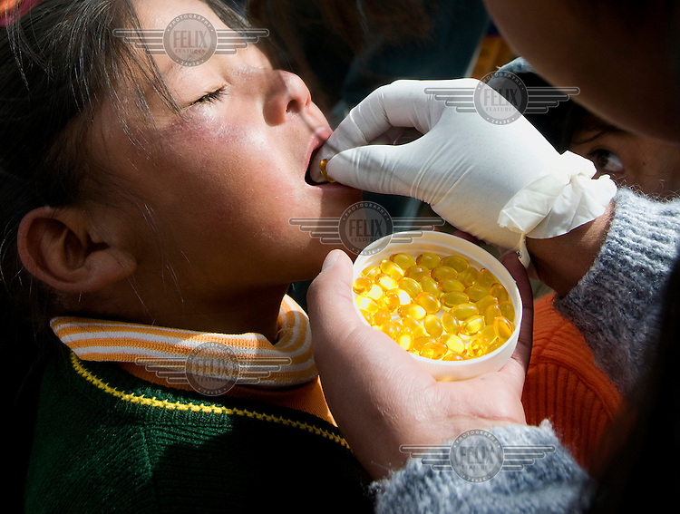 A child is given a vitamin D rich oil capsules at El Alto primary school.