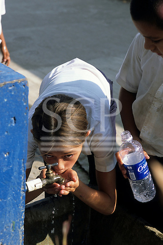 Osa Peninsula, Costa Rica. Teenage girl taking a drink from a standpipe tap, boy with empty mineral water bottle.