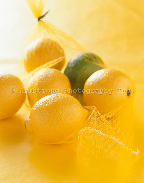 A bag of lemons with one lime, on a yellow background