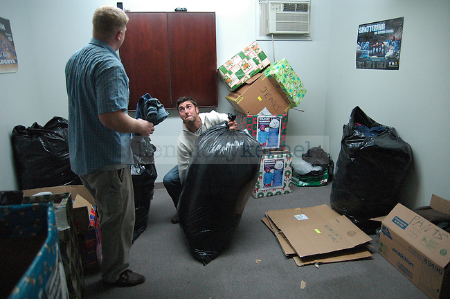 Public Health Graduate students Joe Bell (left) and Jacob Sither talk as they finish sorting all the clothes donated to the Wildcat Warmth project at the Reynolds building on Thursday, November 12th 2009. Photo by Jon Reynolds | Staff