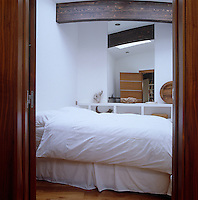 Mirrors and a large skylight give this otherwise small and compact bedroom a sense of light and space