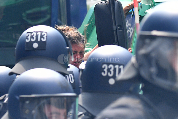 A female protestor is surrounded by police in riot gear after being pepper-sprayed during demonstrations against the G20 summit in Hamburg, Germany, 7 July 2017. The summit, a meeting of the governments of the twenty largest world economies, begins on the 7 July and concludes on the 8 July. Photo: Boris Roessler/dpa /MediaPunch ***FOR USA ONLY***