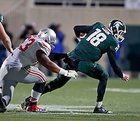 Ohio State Buckeyes defensive tackle Michael Bennett (63) throws down Michigan State Spartans quarterback Connor Cook (18) for a sack during the 4th quarter at Spartan Stadium in East Lansing, Michigan on November 8, 2014.  (Dispatch photo by Kyle Robertson)