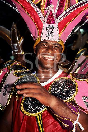Rio de Janeiro, Brazil. Man wearing an  elaborate costume themed on money with a large headdress with dollar signs; Samba school, Carnival.
