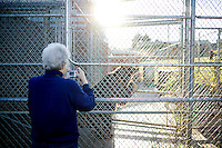 A visitor outside of the Bear Research Center on Washington State University's campus in Pullman, Wash. takes a photograph of a grizzly bear through the double chain-link fence. ..(Matt Mills McKnight for The Wall Street Journal)