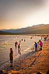Crowds of people fishing for hooligan with nets at Twenty Mile River at sunset. Portage, Southcentral Alaska, Summer. Vertical.