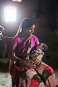 22 year old Seema Devi seen with her 3 months old son, Krishna in her hut in Khurmaniya village in Raxaul district of Bihar. Seema Devi lost 5 of her children and her 6th child, Krishna was born in a government hospital. She is doing everything to make sure her son stays healthy.
