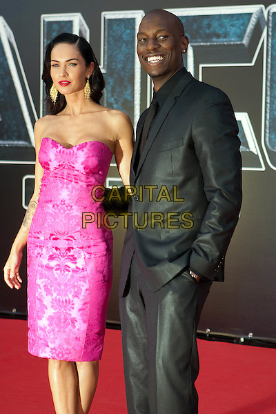 Megan Fox & Tyrese Gibson.Transformers: Revenge of the Fallen Film Premiere, Moscow, Russia..June 16th, 2009.half length pink strapless dress 3/4 black suit gold dangling earrings.CAP/PER/AB.©AB/PersonaStars/CapitalPictures
