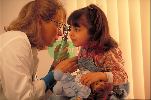 female doctor examining young girl's ear with otoscope