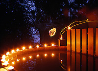 Outdoor candles illuminate the curved edge of the wooden hot tub