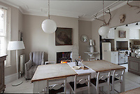 Two simple, orb ceiling lights are suspended over the rustic dining table and chairs