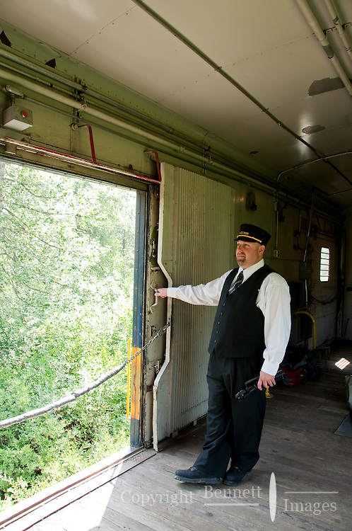 The conductor waits as the train slow to a stop, ready to help returning campers and hikers load their gear.