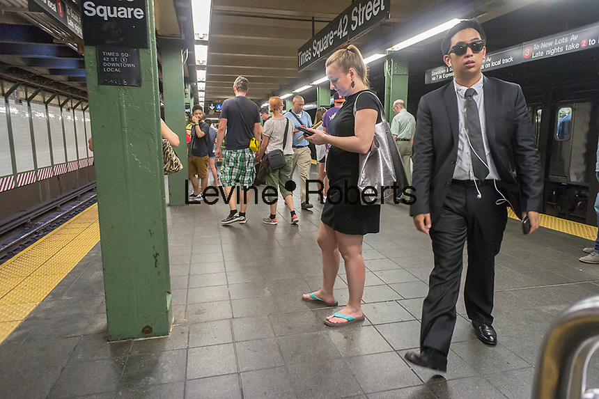 A woman uses her tablet computer on the busy Times Square subway platform while waiting for a train in New York on Thursday, September 12, 2013. (© Richard B. Levine)