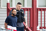 WATERBURY,  CT-051719JS10-  Waterbury police take a resident into custody from a home on Bishop Street as police, along with cooperation from State Police, Watertown Police, the States Attorney's Office, the DEA and ATF, conducted search and seizures as well as searching for wanted suspects who police say were suspected in the sale of heroin.<br /> Jim Shannon Republican American