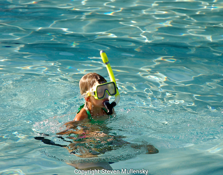 Travel: A young girl surfaces to take a break from spotting exotic fish of the coast of Maui.