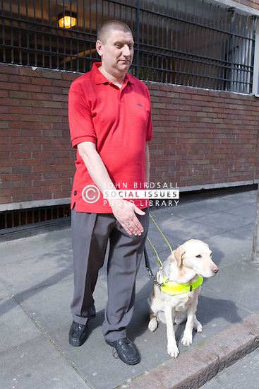 Vision impaired man and guide dog prepare to cross a road,