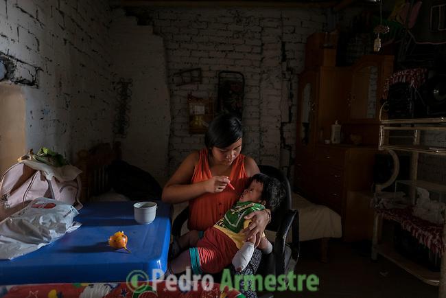 2015-03-04. UN &Aacute;NGEL CON LAS ALAS PEGADAS. &copy; Calamar2/Susana HIDALGO &amp; Pedro ARMESTRE<br />  Evelyn, de 14 a&ntilde;os, da la comida a su hermano &Aacute;ngel C&eacute;sar el d&iacute;a que regresa a casa tras la intervenci&oacute;n m&eacute;dica. <br />    &Aacute;ngel C&eacute;sar Alonso, de 10 meses, naci&oacute; por ces&aacute;rea en Chiclayo (Per&uacute;) y los m&eacute;dicos le diagnosticaron s&iacute;ndrome de Apert, una enfermedad gen&eacute;tica que afecta a la forma de la cabeza y que hace que el peque&ntilde;o tenga los ojos abultados y padezca sindactilia (los dedos de las manos y de los pies pegados). El s&iacute;ndrome de Apert es una de las 7.000 enfermedades raras que existen en el mundo y su prevalencia oscila entre 1 y 6 casos por cada 100.000 nacimientos. La historia de este beb&eacute; es la historia de unos padres coraje, C&eacute;sar Cruz y Edita Jim&eacute;nez, que se desviven para que el peque&ntilde;o pueda tener la mejor calidad de vida posible. C&eacute;sar y Edita acudieron el pasado mes de marzo junto a su beb&eacute; al hospital San Juan de Dios, en Chiclayo, al reclamo de una campa&ntilde;a solidaria de intervenciones quir&uacute;rgicas organizadas por la Sociedad Espa&ntilde;ola de Cirug&iacute;a Pl&aacute;stica, Reparadora y Est&eacute;tica (Secpre) y la ONG Juan Ciudad. Los cirujanos espa&ntilde;oles le operaron las manos para separar unos dedos de otros. La intervenci&oacute;n dur&oacute; aproximadamente una hora y media y el peque&ntilde;o necesit&oacute; de curas posteriores.<br /> La operaci&oacute;n fue el primer paso en la mejora de la salud de &Aacute;ngel. Necesitar&aacute; al menos otra m&aacute;s para separar los dedos de los pies. Sus padres son humildes y apenas tienen recursos.  C&eacute;sar, el padre, trabaja levantando casas de adobe. Edita, la madre, vive para su hijo y le gustar&iacute;a en un futuro retomar su profesi&oacute;n de enfermera. &copy; Calamar2/Pedro ARMESTRE<br /> <br />  AN ANGEL WITH 
