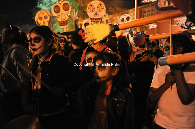 Revelers during community arts organization ElevArte's Dia de los Muertos celebration in Dvorak Park in the Pilsen neighborhood in Chicago, Illinois on November 2, 2015.  Dia de los Muertos is the Mexican celebration of the Catholic holiday known as All Souls Day, which comes after All Saints Day and honors the dead.