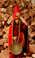Student Buddhist Lama Monk carrying a gong and preparing for a Losar procession, Sikkim, India
