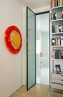 A bright red and yellow plastic wall light creates a sunburst of colour on the white walls of a bedroom in a house designed by Richard Rogers