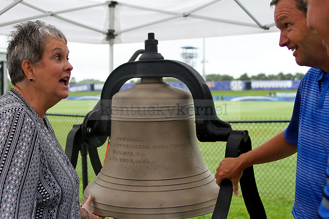 """Mitch Barnhart and Vickie Bell examine the new """"Wildcat Victory Bell"""" up close during the dedication ceremony of the Wendell and Vickie Bell Soccer Complex in Lexington, Ky., on Sunday, August 31, 2014. Photo by Jonathan Krueger 