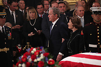 Former President George W. Bush walks past the casket with his wife former first lady Laura Bush during services for his father former President George H.W. Bush in the U.S. Capitol Rotunda in Washington, U.S., December 3, 2018. <br /> CAP/MPI/RS<br /> &copy;RS/MPI/Capital Pictures