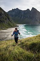 Female hiker hiking up trail with Kvalvika beach in background, Moskenesoy, Lofoten Islands, Norway