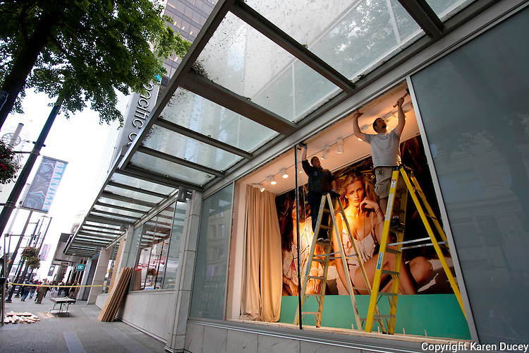 Steve Cox (right) and David Shaw, both from Maple Ridge, BC,  take measurements to board up a vandalized window at the H & M store in downtown Vancouver, BC on June 16, 2011.  Working for Extreme Glass, Shaw estimated they have orders to board up around 70 storefronts. Rioters looted stores and burned cars after the Canucks' loss to the Boston Bruins in last night's Stanley Cup.  (photo copyright Karen Ducey 2011)