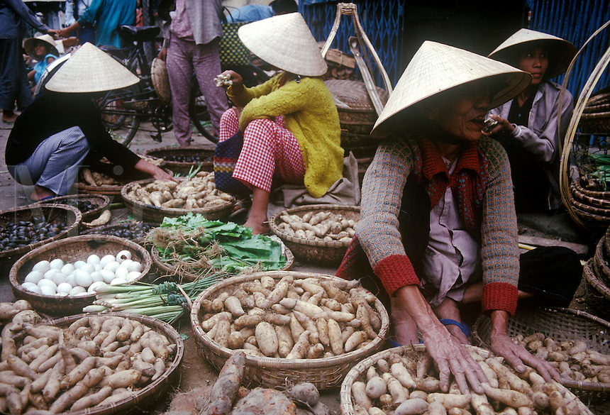 Vietnamese women peddle thier eggs , onions and potatoes in open market.