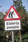 Red triangle road sign showing image of two old people and words Elderly People